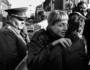 Scène de retrouvailles entre un citoyen de Berlin-Est et une femme de Berlin-Ouest sous les yeux d'un soldat Est-allemand.
