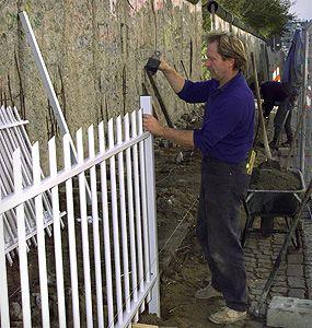 Dix ans après la chute du mur, les ouvriers installent une nouvelle clôture protectrice devant une partie  du Mur