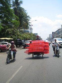 Dans les rues de Phnom Penh, transport de chaises en plastique