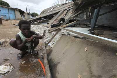 Une petite fille buvant de l'eau à même le sol du quartier dévasté de Yopougon à Abidjian