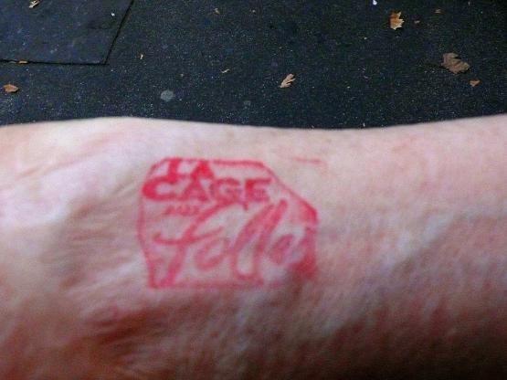 A l'entracte, le spectateur qui sort se voit tatouer l'avant-bras .
