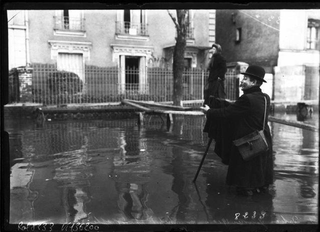 Agence ROL : photographe les pieds dans l'eau, lors des inondations de Paris, 1910