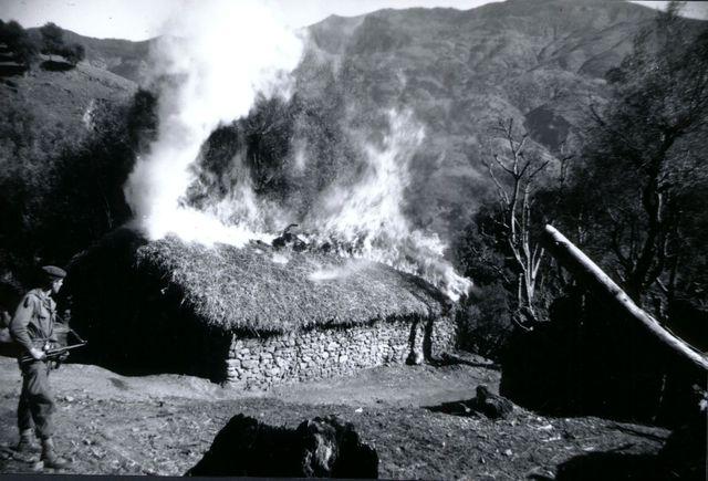 Soldat français devant une maison en feu pendant la Guerre d'Algérie