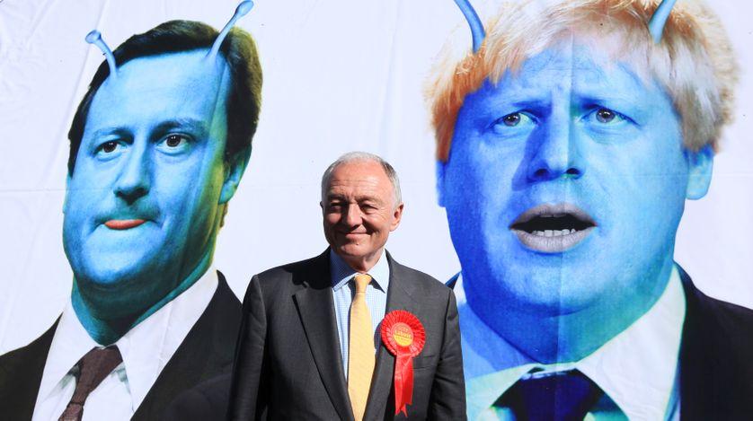 Le candidat travailliste Livingstone devant un poster caricaturant le premier ministre Cameron et le candidat conservateur Johns