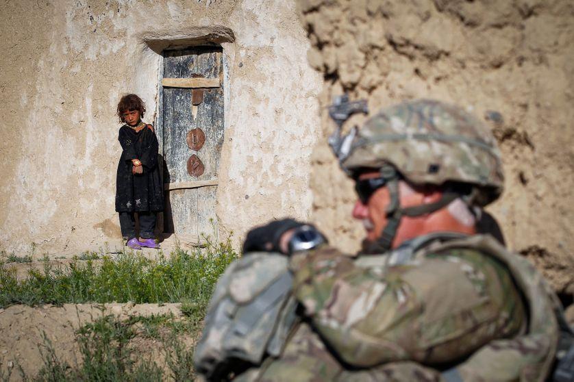 Une enfant regarde un soldat américain qui patrouille dans le village de Kherwar, le 19/05/