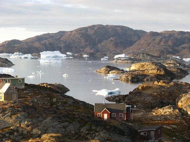 Petit village inuits abandonné avec au loin des icebergs