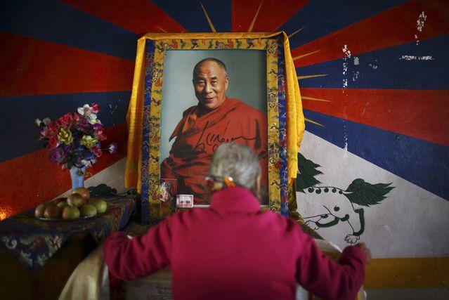 Une Tibétaine devant un portrait du Dalaï-Lama