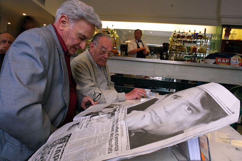 Des personnes lisent les journaux qui titrent sur le retour de Bernard Tapie à l'OM