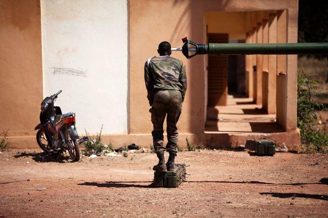 Un soldat français regarde dans le canon d'un tank à une base aérienne du Mali à Bamako
