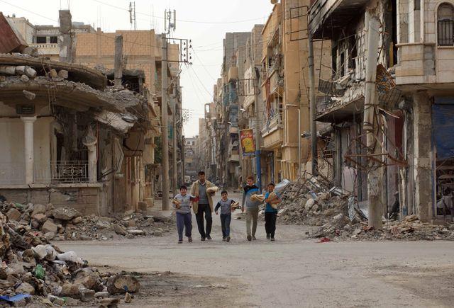 Une famille dans les rues dévastées de Deir al-Zor, Syrie