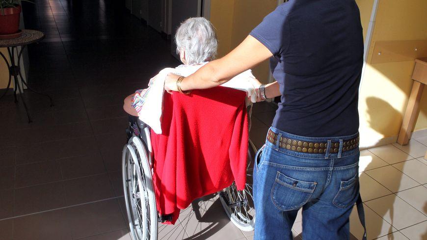 Une aide soignante déplace une personne âgée dans son fauteuil roulant.