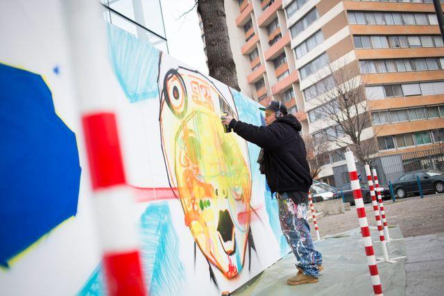 L artiste MARKO93 realise une performance de graff en marge du forum.