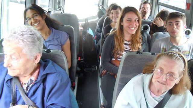 Personnes âgées et étudiants solidaires dans le minibus en route pour le supermarché