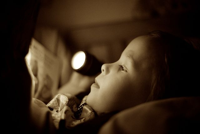 Little boy reading by torchlight