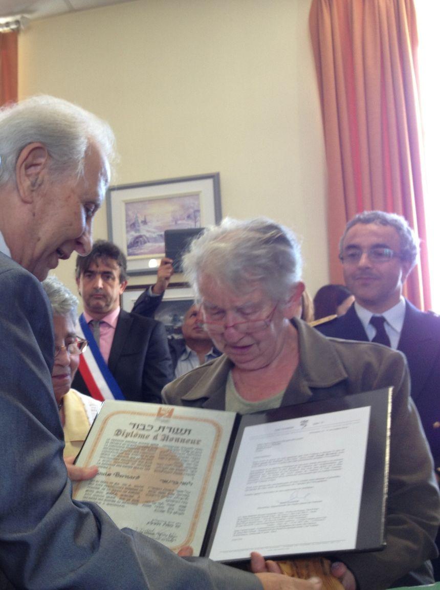 """La Nièce de """"Jojo"""" Bernard recevant le diplôme de Juste parmi les Nations attribué à son oncle"""