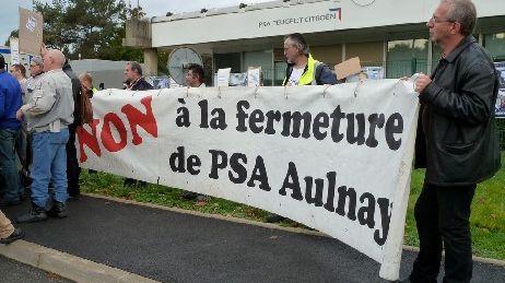 Des salariés du site PSA d'Aulnay manifestent contre la fermeture, à l'occasion de la sortie de la dernière voiture