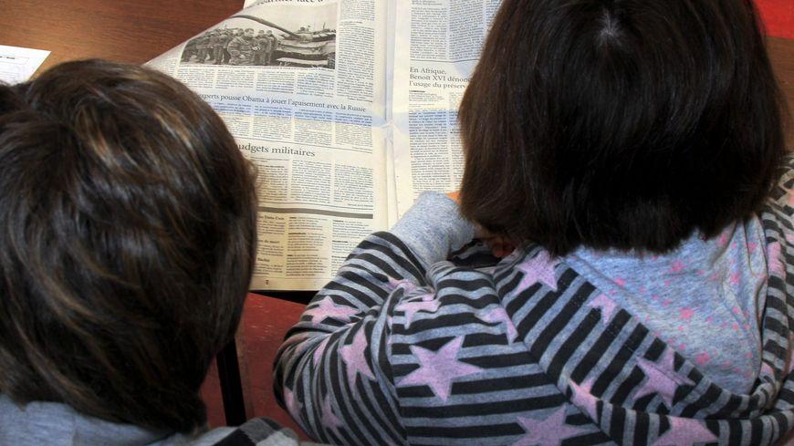 Des enfants parcourent un journal local.