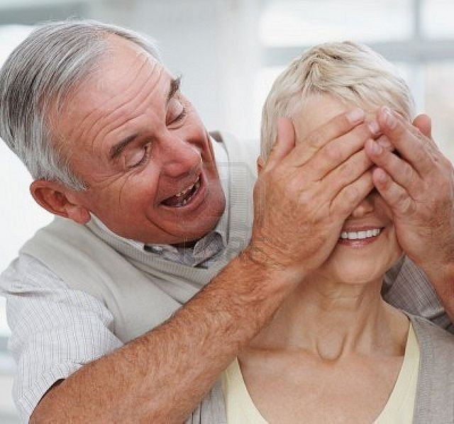 senior-couple-in-a-playful-mood- -husband-covering-wife-s-eyes