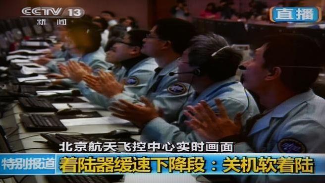 Des opérateurs du centre spatial chinois de Pékin célèbrent l'alunissage de la sonde Chang'e 3