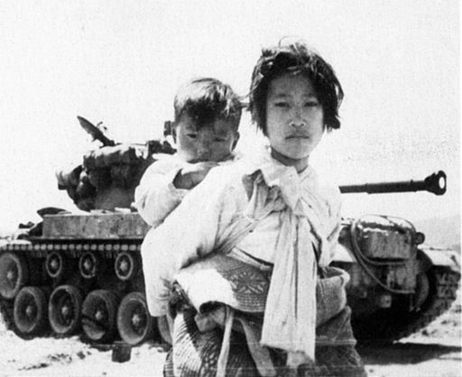 With her brother on the back a war weary Korean girl trudges by a stalled M-26 tank, at Haengju, Korea. June 9,1951