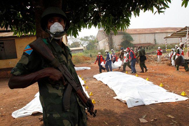Un soldat de la force africaine protège l'évacuation de corps par la Croix-Rouge, dans la banlieue de Bangui.