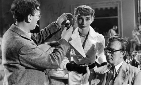 Douglas Slocombe, left, checks light levels with Audrey Hepburn on the set of The Lavender Hill Mob, 1951.