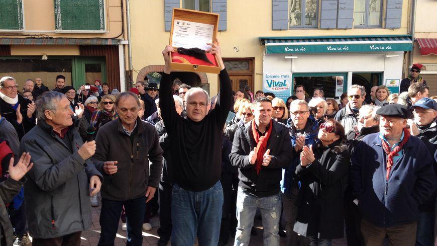 Le maire de Prats-de-Mollo brandit la patte de l'ours juste avant le lancement de la fête