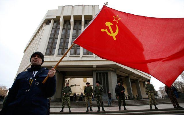 A Simferopol , devant le parlement un homme brandit un drapeau russe