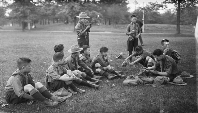 Chinese Boy Scouts eating lemons in High Park, Toronto, Ontario. June 8, 1919