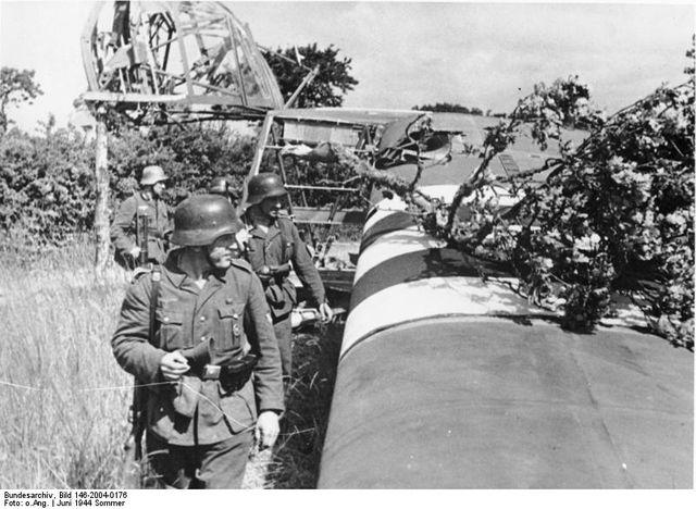 Soldats allemands inspectant un planeur détruit
