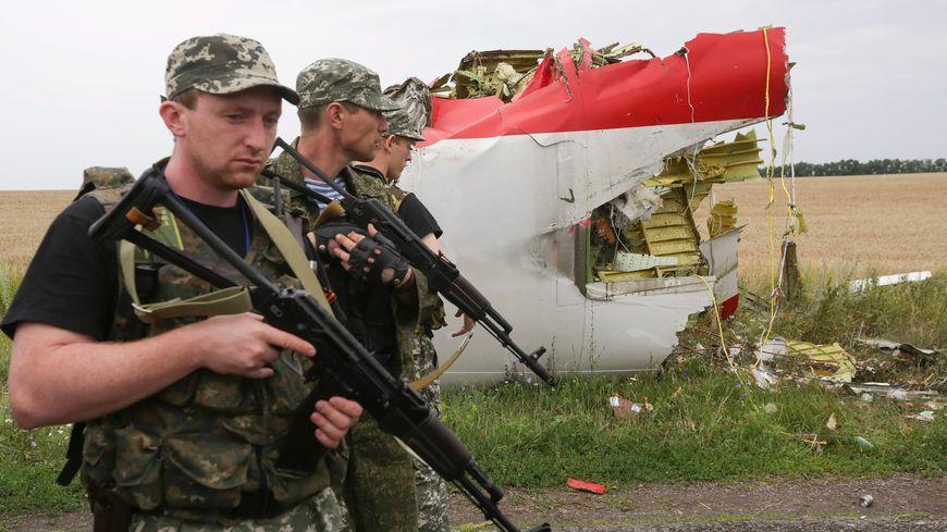 Des militaires prorusses passent devant les décombres du vol MH17