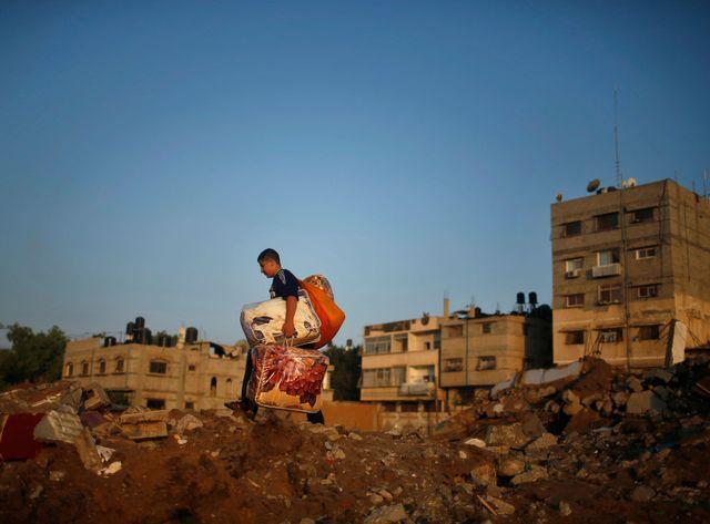 Un jeune palestinien au milieu des décombres de sa maison après un raid israélien