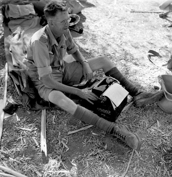Canadian Press war correspondent Ross Munro typing a story in the battle area between Valguarnera and Leonforte, Italy, August 1
