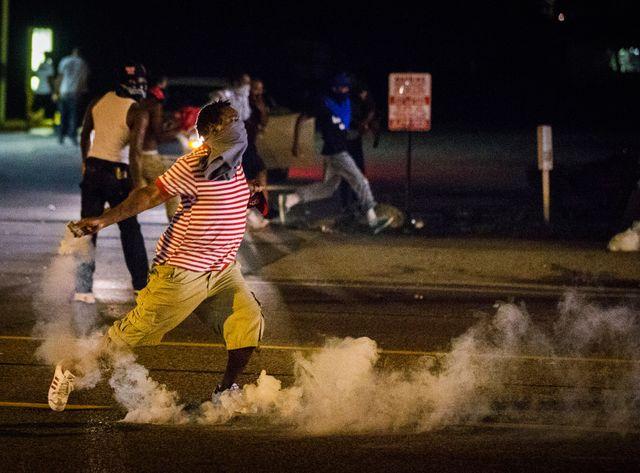 Un manifestant renvoie du gaz lacrymogène vers des policiers, ce dimanche.