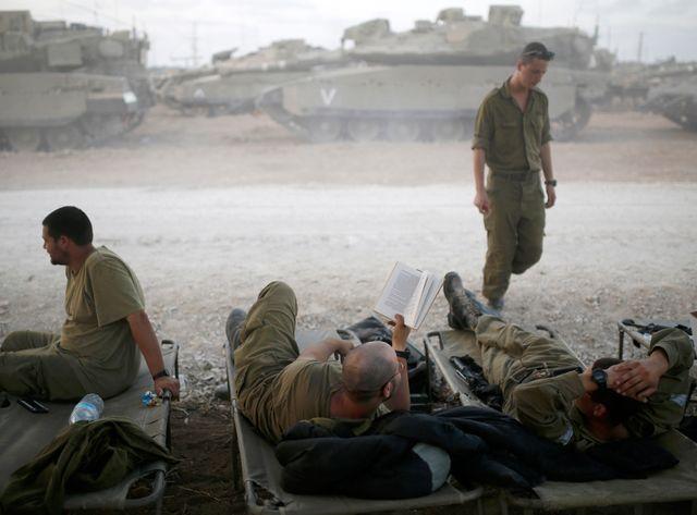 Des soldats isréaliens se reposent, à la limite nord de la bande de Gaza.