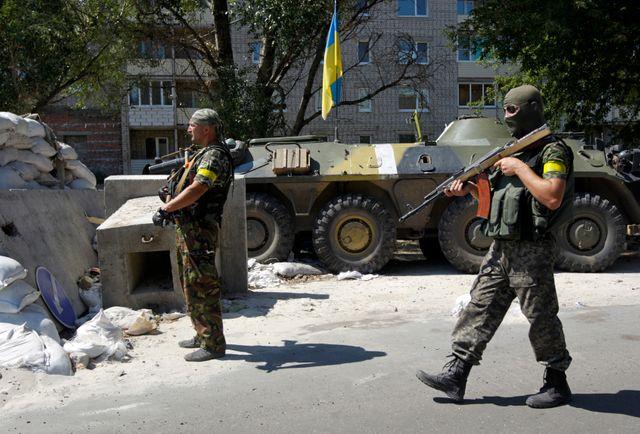 des militaires ukrainiens gardent un point de contrôle en dehors de Donetsk