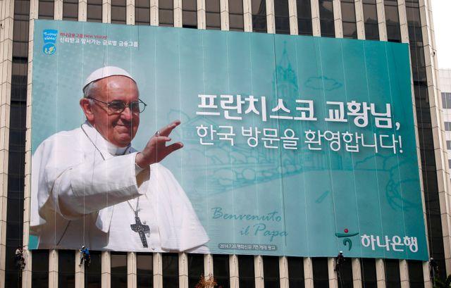 Les ouvriers installent une banderole géante représentant le pape et un message de bienvenue