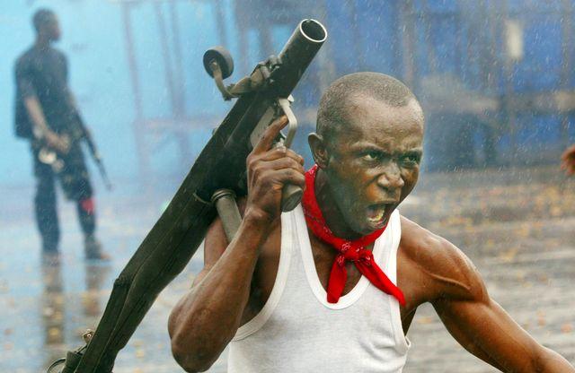 Monrovia, Liberia, 23 juillet 2003. Cri de guerre. Ce soldat des forces pro-gouvernementales vient de tirer une roquette sur les