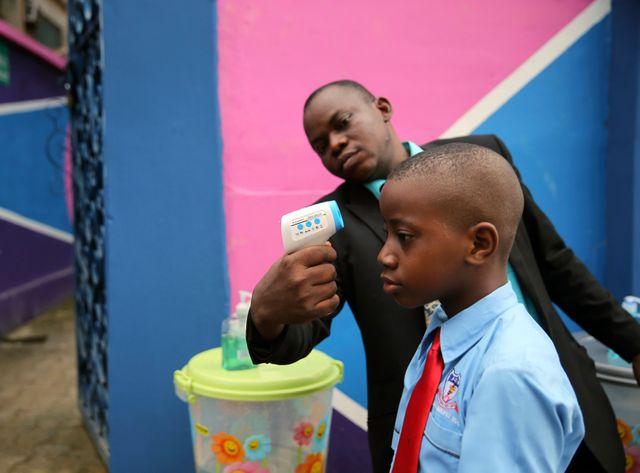 Un homme contrôle la température d'un jeune garçon à l'entrée d'une école de Lagos au Nigéria