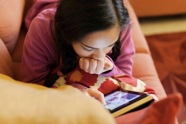 Jeune fille lisant un livre numérique