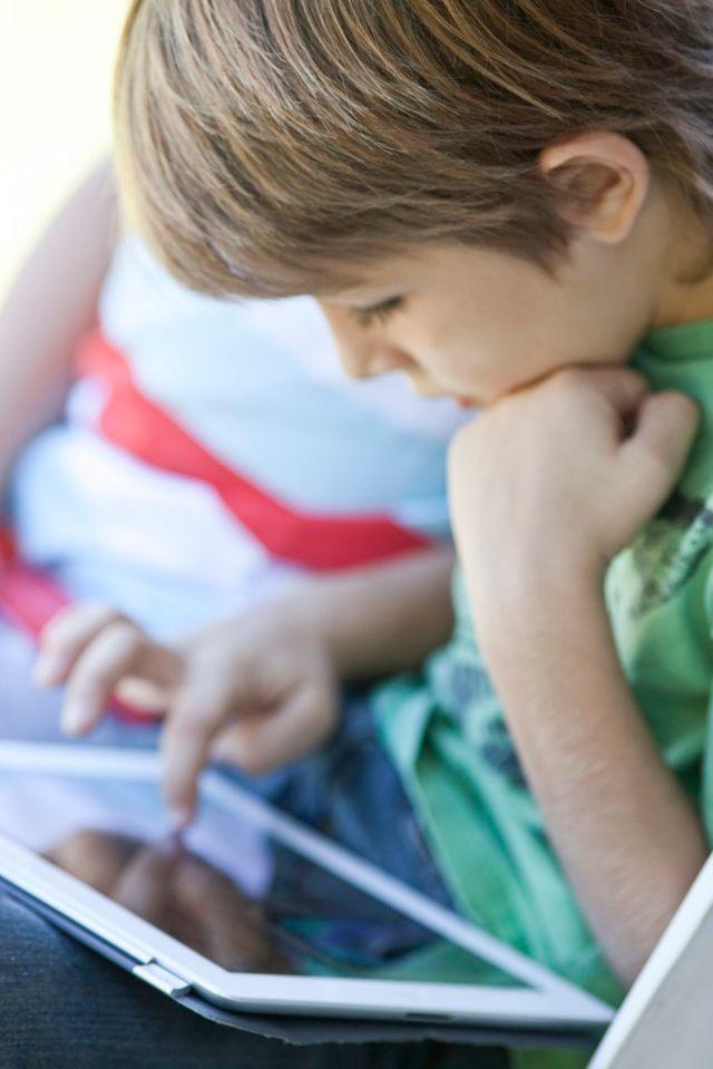Jeune garçon lisant sur une tablette numérique
