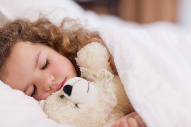 Jeune fille dormant avec sa peluche