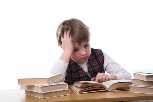 Un enfant devant ses livres, exaspéré