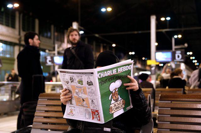 Un homme lit Charlie Hebdo a la Gare de Lyon