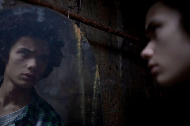 Jeune homme se regardant dans le miroir