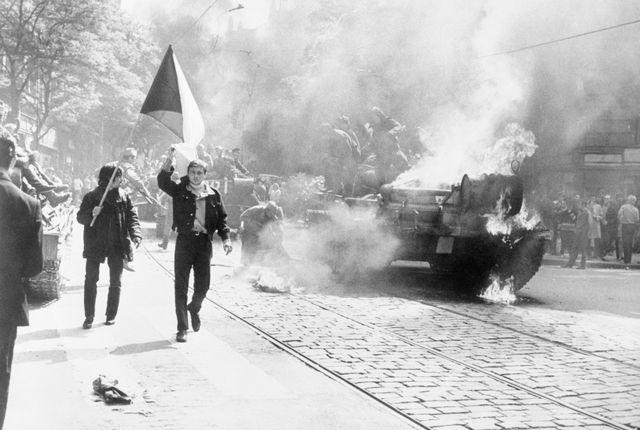 Prague: Czechoslovaks, 21/12/1968. Jeune tchèque portant le drapeau national, à côté d'un char soviétique qui brûle.