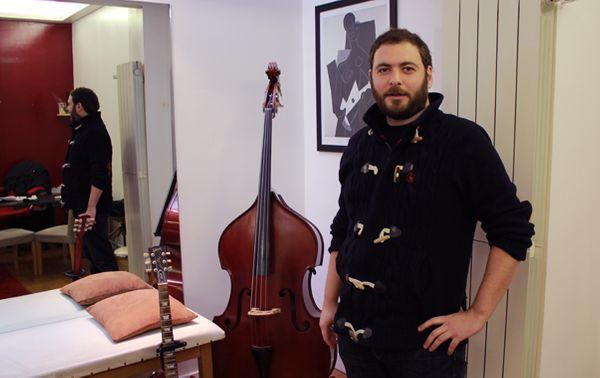 Le kinésithérapeute Florian Chrétien dans son cabinet qui ressemble à s'y méprendre à un magasin d'instruments de musique. (© Victor Tribot Laspière / France Musique)