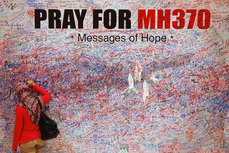Femme inscrivant un message de soutien aux familles des disparus du MH370, le 16 mars 2014, à Kuala Lumpur, en Malaisie
