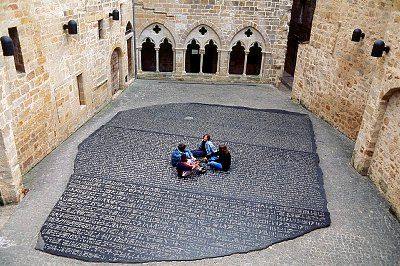Adolescents assis sur une grande copie de la pierre de Rosette (Musée Champollion à Figeac)