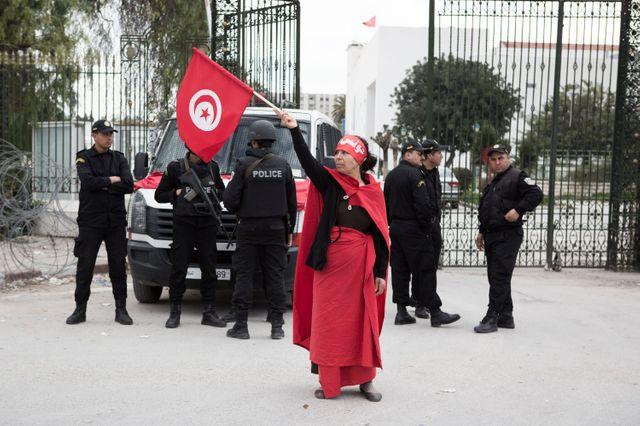 Une femme brandit le drapeau tunisien devant le musée du Bardo où 21 personnes ont été tuées lors de l'attentat, Tunis, 20/03/15